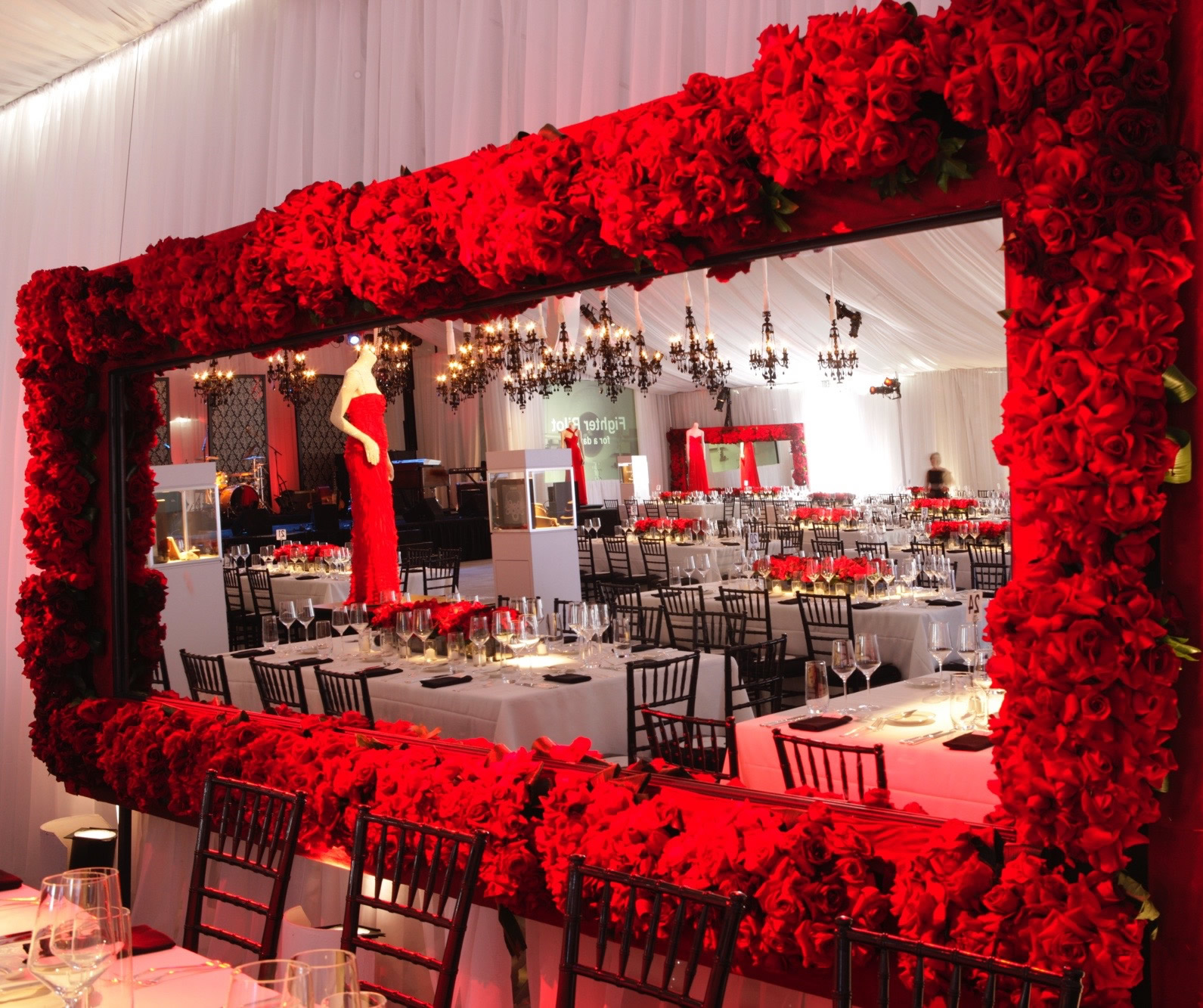 exhibition event management Valentino at Valenti International fundraiser event planning seating and mannequin with red evening dress rose arrangement around mirror